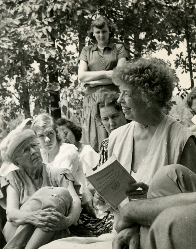 Eleanor Roosevelt holds a copy of the Universal Declaration of Human Rights; Alice K. Pollitzer at left